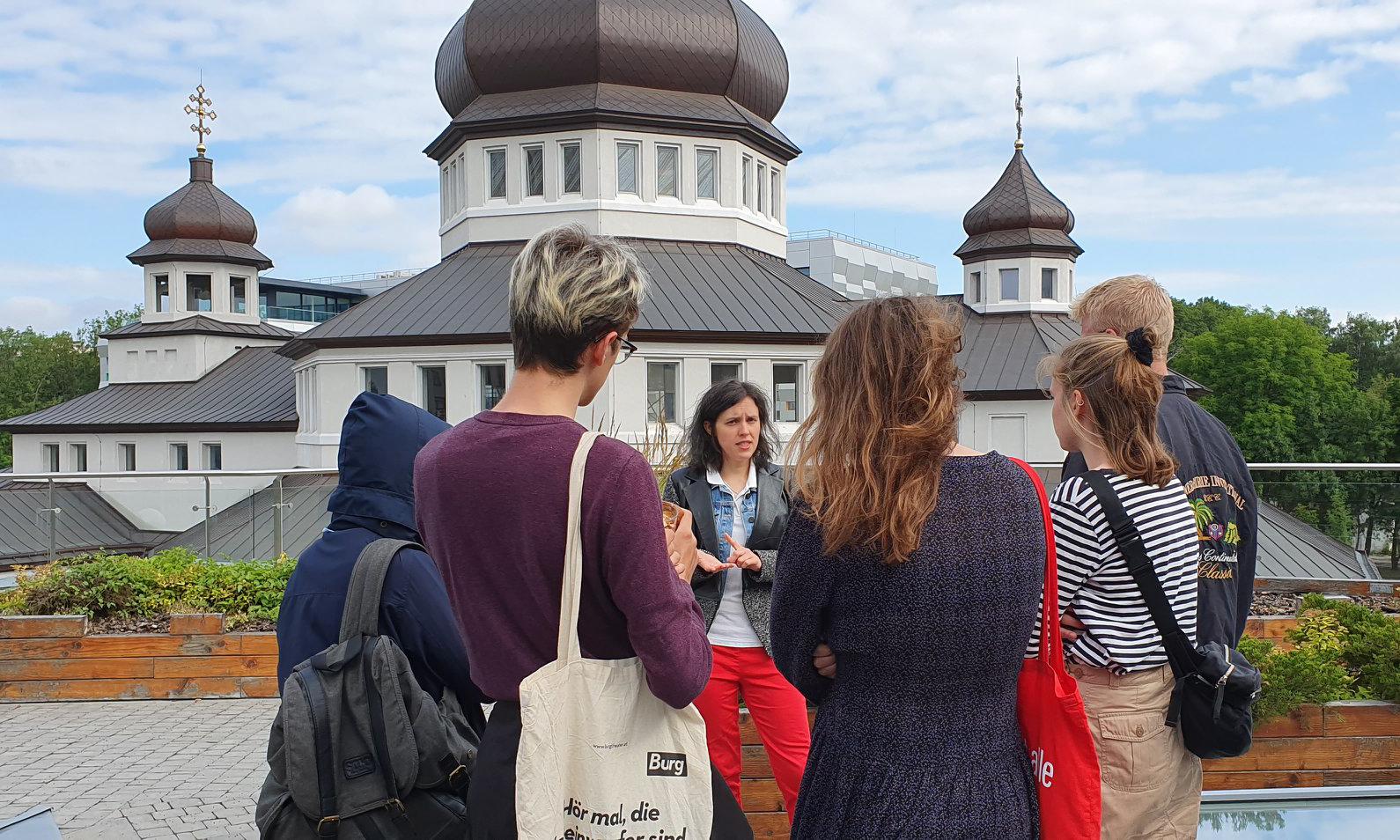 TeilnehmerInnen der International School of Multimedia Journalism 2019 während einer Führung über den UCU-Campus in Lviv, Ukraine (im Hintergrund die Kirche des Campus).